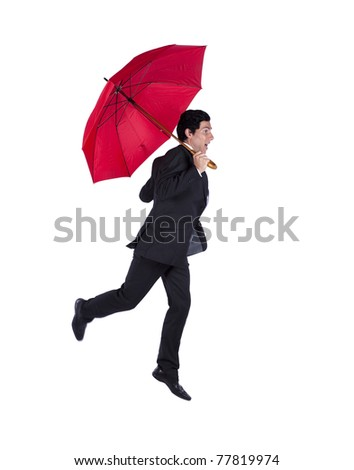 Happy businessman jumping under a red umbrella (some motion blur) - stock photo