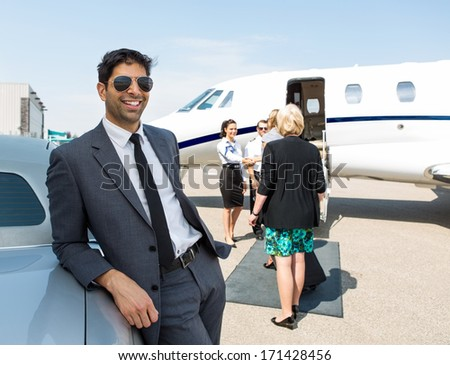 Happy businessman leaning on car with airhostess and pilot greeting business people against private jet - stock photo
