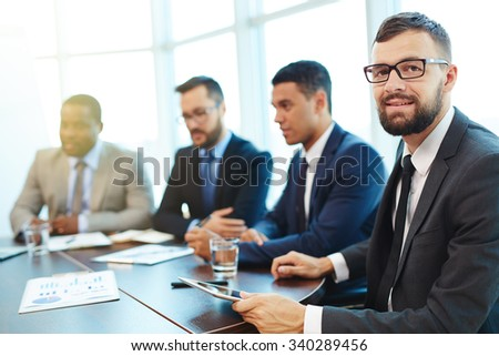 Happy businessman looking at camera at conference with colleagues on background - stock photo
