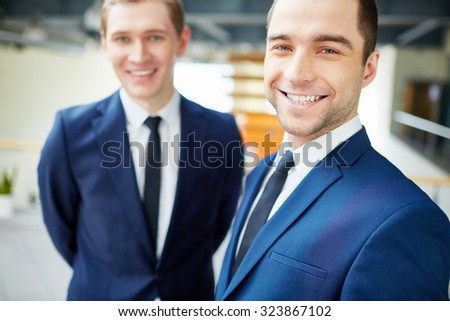 Happy businessman looking at camera on background of colleague - stock photo