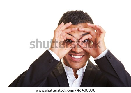 Happy businessman looking through his circled fingers