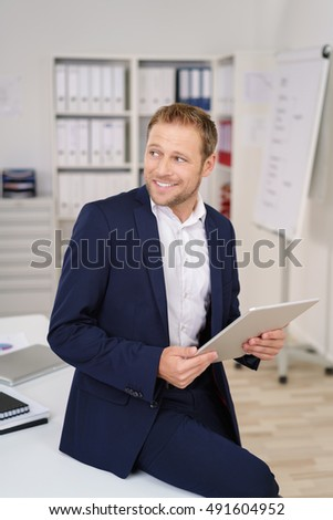 Happy businessman looking to the side watching something in the office as he perches on the edge of his desk holding a document