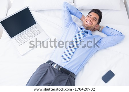 Happy businessman lying on his bed at home in bedroom - stock photo