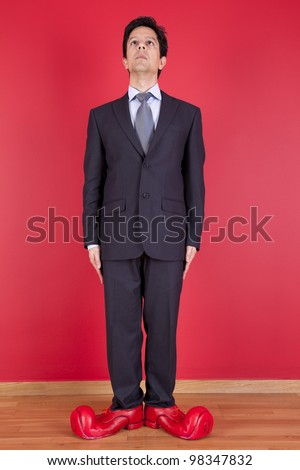 Happy businessman next to a red wall with clown shoes - stock photo