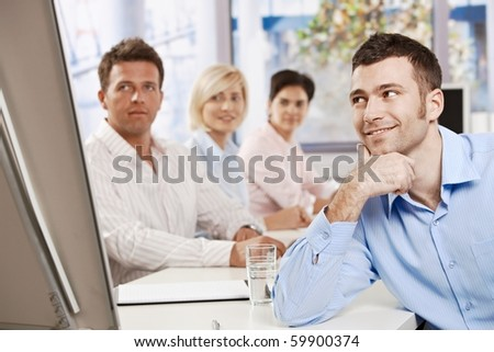 Happy businessman on business meeting at office, leaning on table, looking to whiteboard and smiling.?