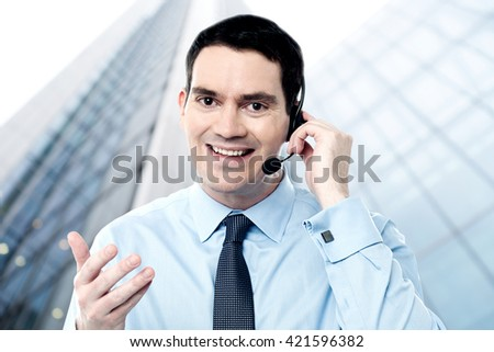 Happy businessman on call outside office building - stock photo