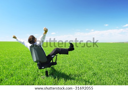 Happy businessman on chair in green field - stock photo