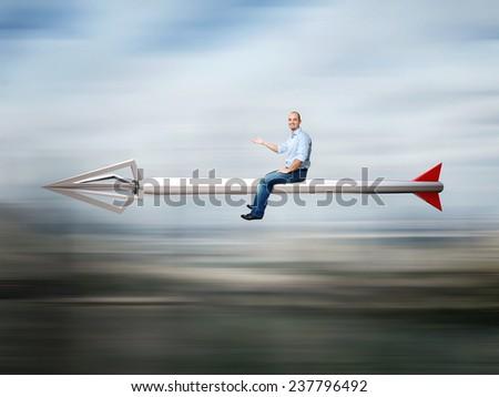 happy businessman on huge metal arrow - stock photo