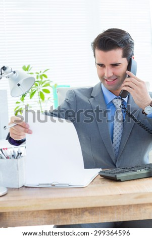 Happy businessman phoning and looking note in the office - stock photo