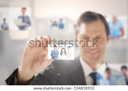 Happy businessman picking a business team picture among blurred others - stock photo