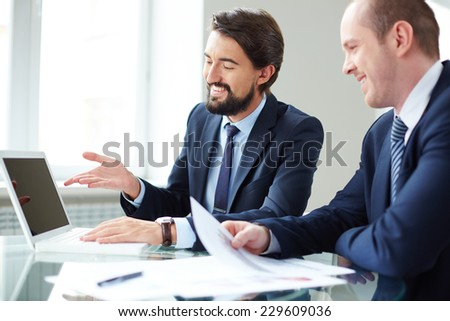 Happy businessman pointing at laptop screen while explaining ideas to his colleague - stock photo