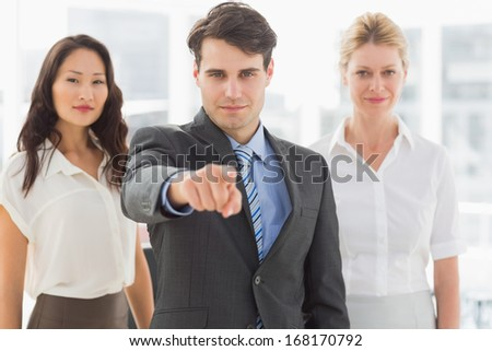 Happy businessman pointing to camera in front of his team in the office