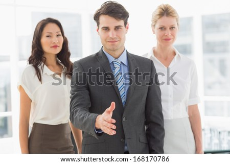 Happy businessman reaching hand out in front of his team in the office