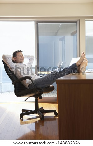 Happy businessman reclining with his feet up on desk - stock photo