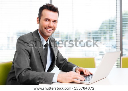 Happy businessman sit at desk in the office. Looking at camera, working with laptop - stock photo