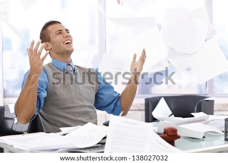 Happy businessman sitting at desk, throwing documents up in air, laughing, celebrating. - stock photo