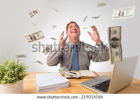 Happy businessman sitting at his desk while money falling on him - stock photo