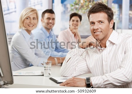 Happy businessman sitting at table in meeting room at office, looking at camera smiling - stock photo
