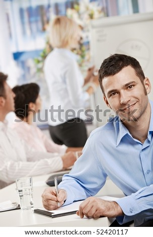 Happy businessman sitting at table in office writing notes on business meeting, looking at camera, smiling.