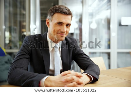 Happy businessman sitting at the table in office - stock photo