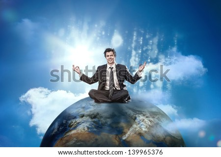 Happy businessman sitting cross legged on top of the world - stock photo
