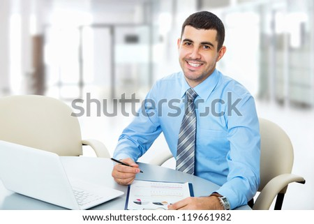 Happy businessman sitting in front of laptop - stock photo