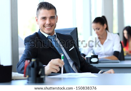 Happy businessman sitting in office  - stock photo