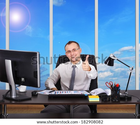 happy businessman sitting in office with thumb up - stock photo