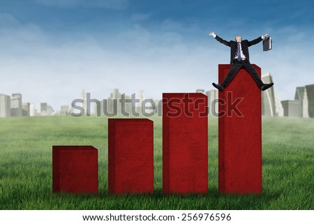 Happy businessman sitting on the highest chart and celebrate his success  - stock photo
