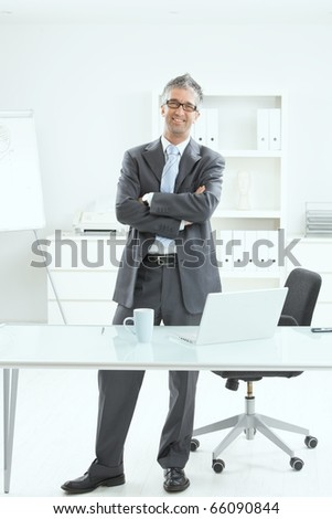 Happy businessman standing at office desk, smiling.?