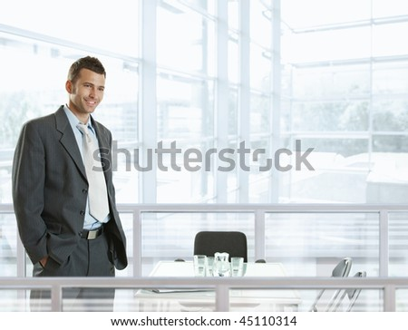 Happy businessman standing behind office desk, smiling. - stock photo