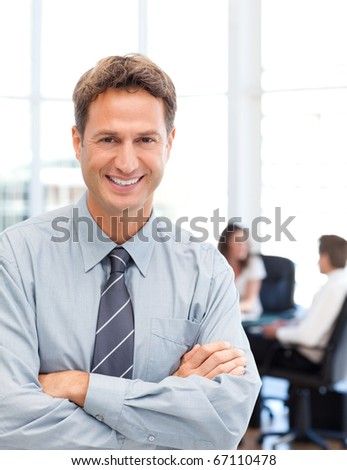 Happy businessman standing in front of his team while working at a table in the background - stock photo