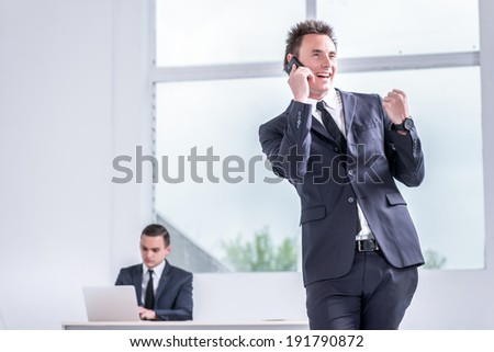 Happy businessman standing in office shouting and rejoicing her success. Young confident man standing and sitting at a desk with a laptop tablet facing window with a view to the street - stock photo