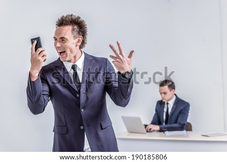 Happy businessman standing in office shouting and rejoicing success. Young confident man standing and sitting at a desk with a laptop tablet