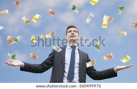 Happy businessman standing in the rain of euro money.  Euro are falling from the sky