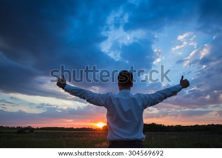 Happy businessman standing on the field to face the sunset - stock photo