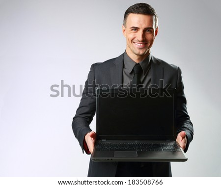Happy businessman standing with laptop on gray background