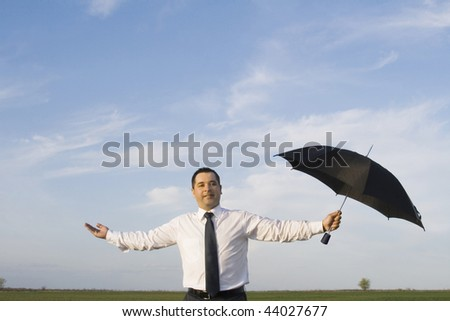 Happy businessman standing with umbrella in the meadow - stock photo