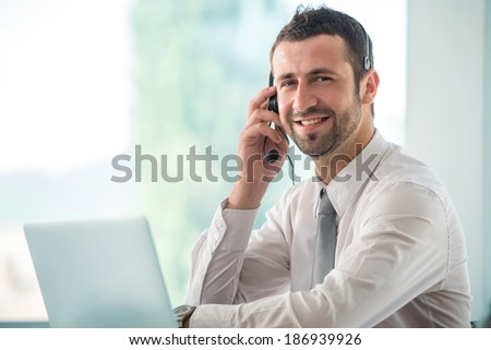 Happy businessman talking on headset in office - stock photo