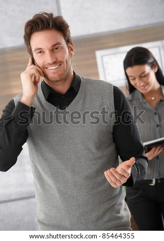 Happy businessman talking on mobile phone, secretary standing behind.? - stock photo