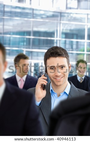 Happy businessman talking on mobile standing in crowd in office lobby. - stock photo