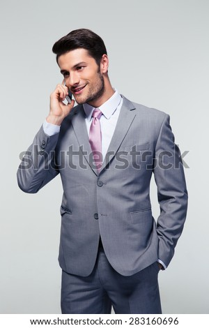 Happy businessman talking on the mobile phone over gray background. Looking away - stock photo