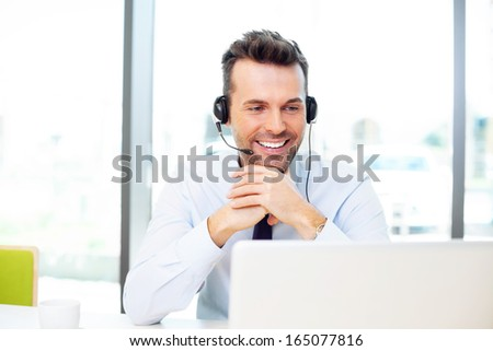 Happy businessman talking with headset - stock photo