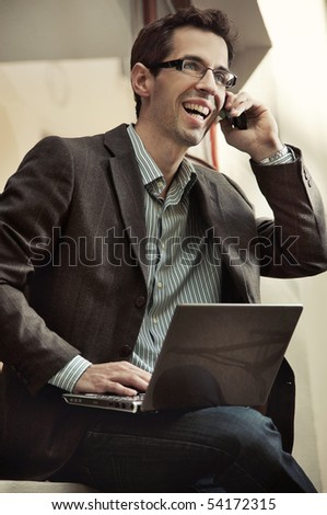 Happy businessman using cellphone in the city - stock photo