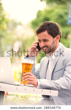 Happy businessman using mobile phone and laptop while holding beer glass at outdoor restaurant - stock photo