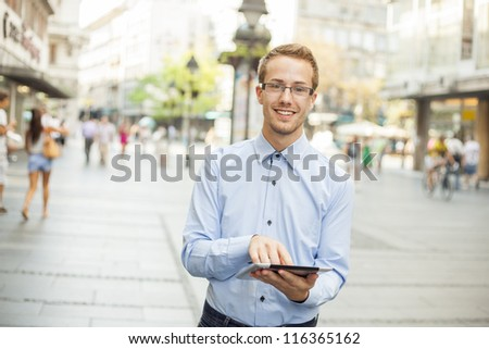 Happy Businessman Using Tablet Computer in public space - stock photo