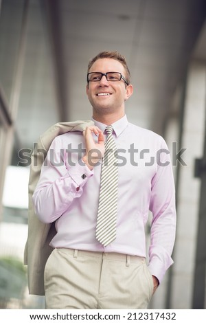 Happy businessman walking with jacket over his shoulder - stock photo