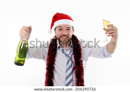 Happy businessman wearing a santa hat with tinsel around his neck in a blue business shirt and blue tie holding a bottle and glass of champagne drinking at his christmas party on white background - stock photo