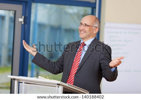 Happy businessman with arms raised standing at podium in office - stock photo