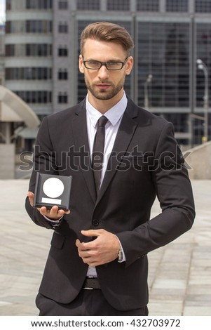 Happy Businessman with award on urban background